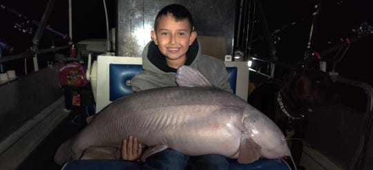 Alex Flores, 9, sits with a 42-pound blue catfish he caught at Elephant Butte Reservoir Sunday, Nov. 10.