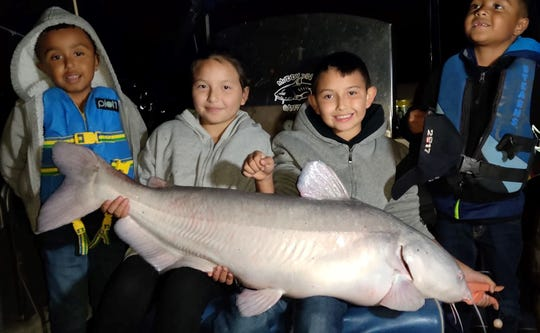 From left to right, Jaycion Sanchez, Jenna Trujillo, Alex Flores and Jasias Sanchez sit in a boat holding the 42-pound blue catfish Alex caught at Elephant Butte Reservoir on Sunday, Nov. 10, 2019.