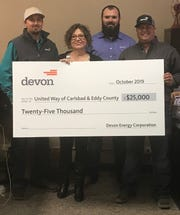 Devon Energy employees Christopher West, Brandon Boyles and Wes Ryan present a $25,000 check to Linda Dodd, director of the United Way of Carlsbad and South Eddy County.