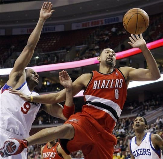 Juwan Howard of the Trail Blazers and Andre Iguodala of the 76ers battle for a loose ball during a game Jan. 20.