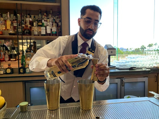 Bartender Raul Lopez prepares a Cloud Nine cocktail at the Thirsty Camel hotel bar inside the Phoenician Resort.