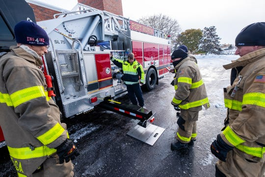 John Hopkins, center, demonstrates to Port Huron firefighters how quickly the jacks on their new truck can deploy during a training session Tuesday, Nov. 12, 2019, at the department's central station in Port Huron.