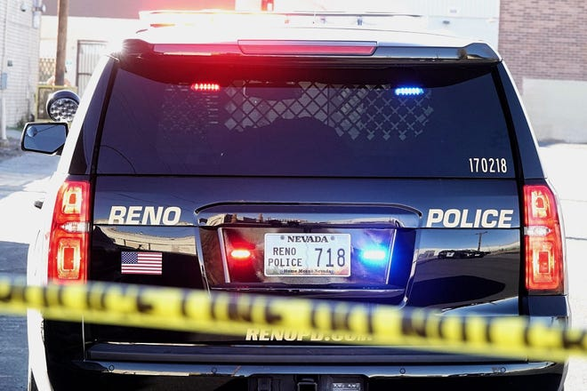 A photo of a patrol vehicle belonging to the Reno Police Department parked behind police tape.