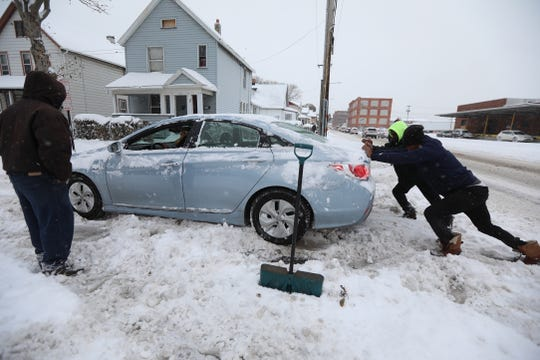 FILE PHOTO: Dwight Green stands aside as Coty Paige and Cornelius McCaley push a car that got stuck in the snow at the corner of Costar St. and Dewey Avenue in Rochester.  Paige and McCaley were on the way to work when they saw the car stuck and pulled over to help the driver out.