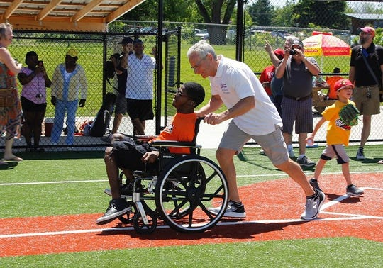 "Ron Kampff and one of his Challenger athletes. Challenger Miracle Field director Katie Kovar said the photo ""captures the essence of all things Ron and the field.''"