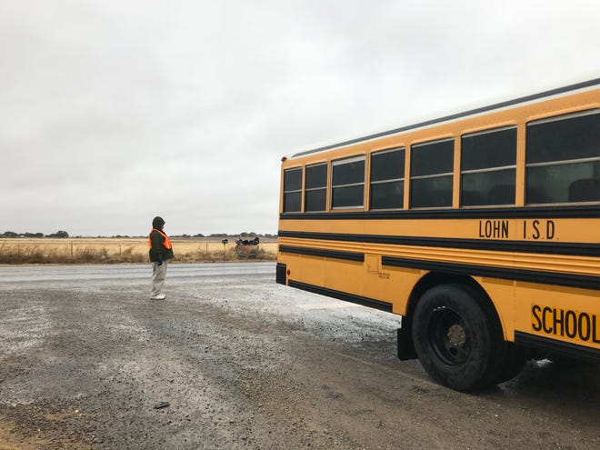 A bus driver for Lohn ISD stands at the intersection of Highway 283 and County Road 166 near Brady, Texas watching for traffic. Parents say the bus stop is 'dangerous' and needs to be moved. Nov. 11, 2019.