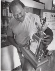 Ralph Powell, a member of the 1950 Blackshear High School state championship football team, admires their trophy during a reunion in 1991.