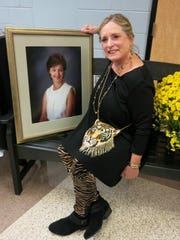 """In  a LSU-inspired ensemble  Berry Glassell, a good friend of the late Anne Higdon, sits with Higdon's photo on a bench dedicated to her in the lobby of CenturyLink Center.   Life Savers 2019 """"Louisiana Saturday Night""""     was held there and  part of the evening's theme was """"Remembering Anne."""""""