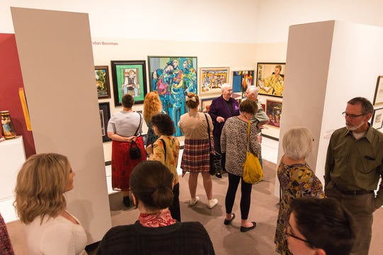 "William Brandon ""Bucky"" Bowman, wearing a purple suit jacket, welcomes Springfield Art Museum patrons to a gallery displaying his personal art collection during the ""Wonder Rooms"" exhibit in 2017."