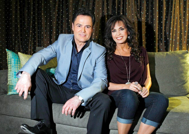 """FILE - In this April 28, 2011 file photo, siblings Donny Osmond, left, and Marie Osmond pose backstage at their show at the Flamingo hotel and casino in Las Vegas. Marie Osmond says she's ready for the final week of an 11-year run with her brother, Donny, at the Flamingo Las Vegas, after telling the audience on her television talk show that she chipped her knee late last week. Osmond talked about her injury during an appearance Monday, Nov. 11, 2019 on """"The Talk."""" She and her brother, who is 62, each have had hits with songs such as 'Puppy Love' and 'Paper Roses.' (AP Photo/Isaac Brekken, File)"""