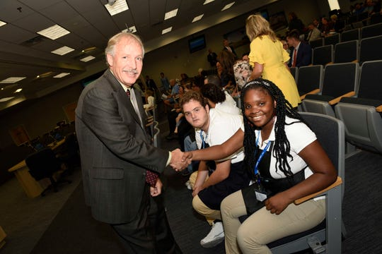 St. Lucie County Administrator Howard Tipton, left, shakes the hand of Student Perks student Jerqueria Fitzgerald.