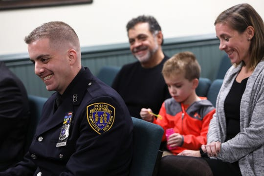 Police officer Arcangelo Liberatore shares a laugh with his wife Alexandra, father Arcangelo Liberatore and son Nico while being recognized for his jiu-jitsu skills before receiving a Lifesaving Award Nov. 12, 2019 at Irvington Justice Court. Officer Liberatore rescued a 5-year-old girl from a rabid coyote while off-duty in a park with his family last year.