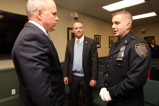 Irvington police officer Arcangelo Liberatore chats with Michael Green, left, executive deputy commissioner of NYS division of criminal justice services, and mayor Brian Smith after receiving a Lifesaving Award Nov. 12, 2019 at Irvington Justice Court. Officer Liberatore rescued a 5-year-old girl from a rabid coyote while off-duty in a park with his family last year.