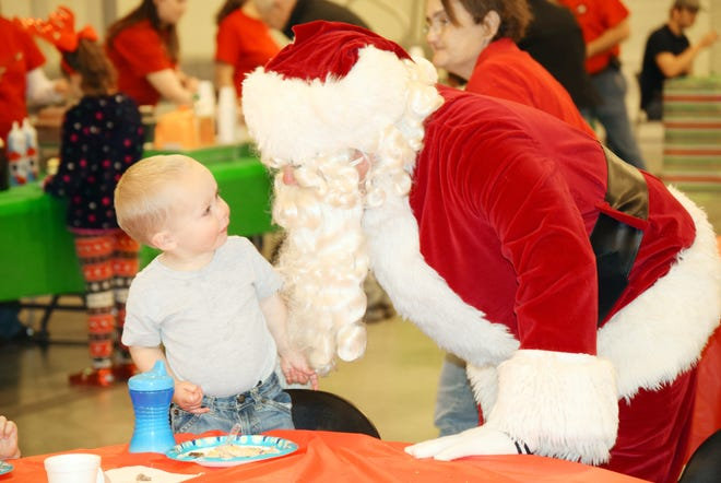 In this file photo, Santa says hello to a new friend at the Bowie Fantasy of Lights Festival. The festival takes place on Dec. 7 with activities all day. Entry forms are now available for those wishing to enter one of North Texas' largest and oldest lighted Christmas parades. Deadline to enter is Nov. 22 with forms available at the BCD office at 101 E. Pecan or visit the group's Facebook page. The parade rolls through town at 7 p.m.