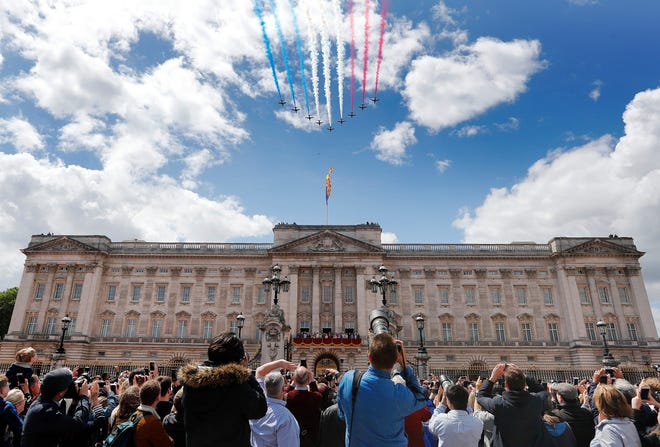 Crowds in London watch a jets trailing Union Jack colors fly over Buckingham Palace at the end of the annual Trooping the Colour parade, June 8, 2019.