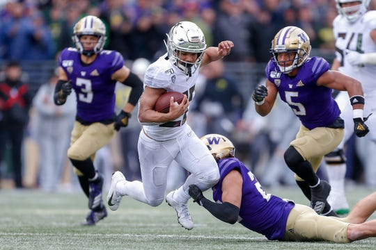Oregon running back Travis Dye tries to avoid a tackle from a Washington defender during the second half at Husky Stadium.