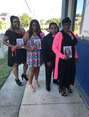 Family members hold pictures of Cathalina Christina James, who was killed in June 2018, at her celebration of life. Siblings (left to right) Tameka, Candace and Mylann James, along with their mother Quenstella James, are waiting for an arrest in the homicide investigation.