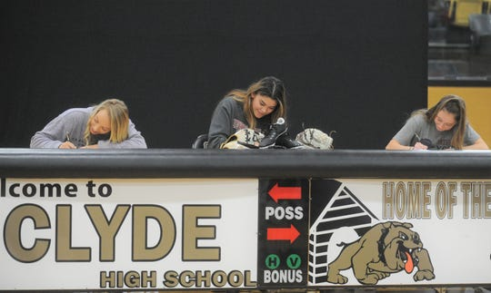From left, Clyde seniors Peyton Lee, Kaitlyn Turner and Megan Smith sign with college programs at a signing ceremony Wednesday, Nov. 13, 2019, at Clyde High School.
