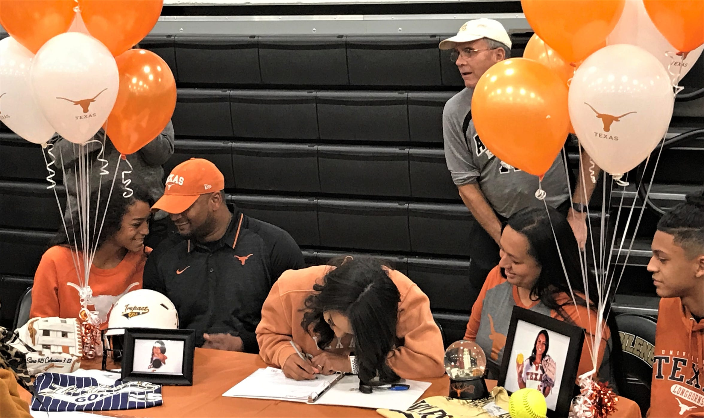 Abilene High senior Alyssa Washington, center, signs a letter-of-intent to play softball at the University of Texas on Wednesday, Nov. 13, 2019, at Eagle Gym.