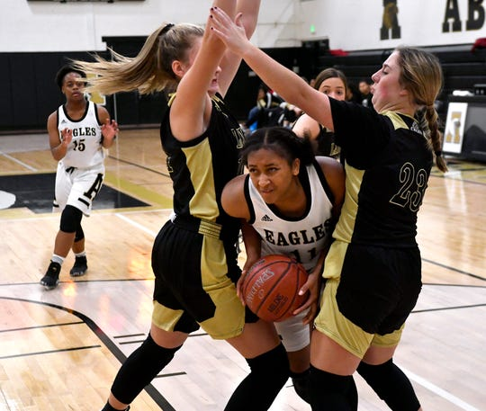 Abilene High's Destiny Potts is sandwiched between Clyde's Liz Underwood and Brynn Burson during Tuesday's basketball game at Eagle Gym Nov. 12, 2019.
