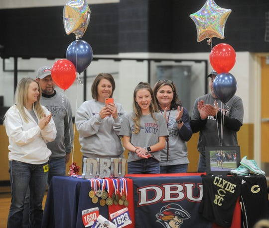 Clyde senior Megan Smith, center, is surrounded by family members during a signing ceremony Wednesday, Nov. 13, 2019, at Clyde High School.