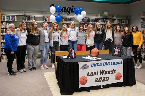 North Buncombe senior Lani Woods poses with the team before signing her letter of intent to play college basketball at UNC Asheville during a ceremony at North Buncombe High School on Nov. 13, 2019.
