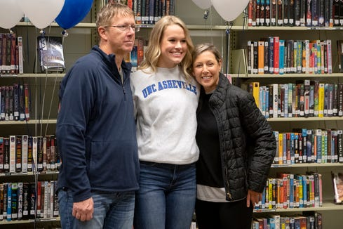 North Buncombe senior Lani Woods poses for a photo with her select travel team coaches Joe Carrington and Jennie West after signing her letter of intent to play college basketball at UNC Asheville during a ceremony at North Buncombe High School on Nov. 13, 2019.