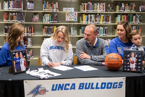 North Buncombe senior Lani Woods sits between her parents Jill Williams and Randy Woods and with her sister Bailey Noland, far right, as she signs her letter of intent to play college basketball at UNC Asheville during a ceremony at North Buncombe High School on Nov. 13, 2019.