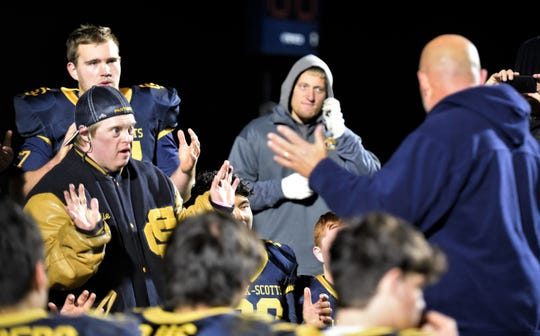 Longtime team manager Eddie Sturm helps head coach Kevin Langs talk to the team following a recent Climax-Scotts football game.