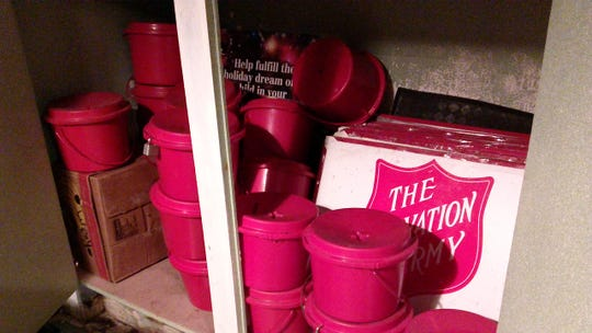 A storage closet with Salvation Army kettles and signs used for the annual fundraising drive.