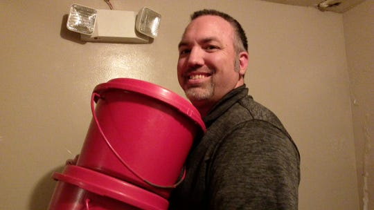 Capt. Joseph Hansen, corps officer for the Salvation Army, Binghamton Center for Worship and Service, takes fundraising kettles upstairs from a basement store room.