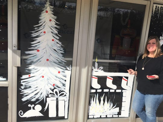 Medford's Heather Henry stands next to window art she painted at CORE Academy of Movement in Mount Laurel. The married mother of four got into art suddenly about three years ago.