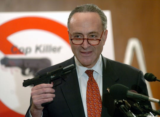 "Sen. Charles Schumer, D-NY holds the Five-SeveN pistol during a news conference about introducing legislation to ban the deadly ""cop killer"" handgun on Thursday, March 3, 2005, in Washington. (AP Photo/Kevin Wolf)"