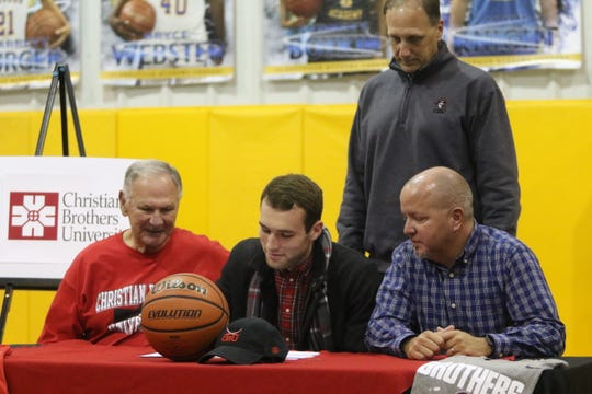 Clarksville Academy's Daniel Loos (center) signs with Christian Brothers on Wednesday as his grandfather, former Austin Peay men's coach Dave Loos (left), father Dave Loos Jr. and Cougars coach Matt Wallace (right) watch.