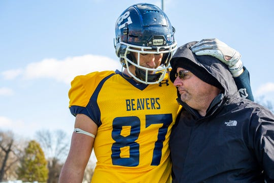 Jordan Travis drapes his arm around his father, Jim Travis of Newton, during the Senior Day program at Buena Vista University on Nov. 2. Jordan Travis is the youngest of seven sons adopted and raised by Jim Travis.