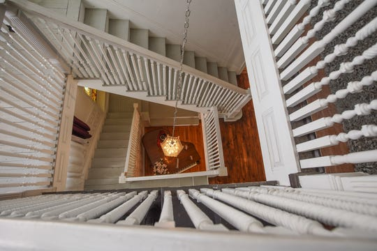 Three stories of a handsome staircase drop from the third floor down to the large entrance hall. Down the long chain a crystal chandelier hangs over a grand piano.