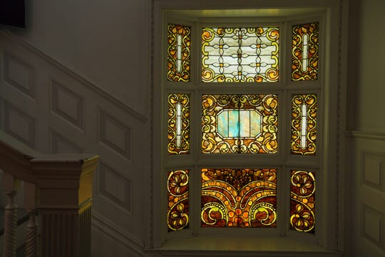 Original stained and leaded glass by the 19th Century artist Julius Melchers is at the base of the three-story staircase. Melchers also carved the exterior stone entrance and two elaborate fireplaces.