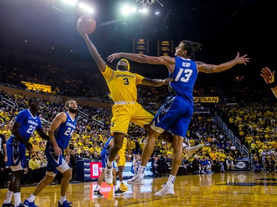 Michigan's Zavier Simpson shoots over Creighton's Christian Bishop in the second half at Crisler Center in Ann Arbor, Mich., Tuesday, Nov. 12, 2019.