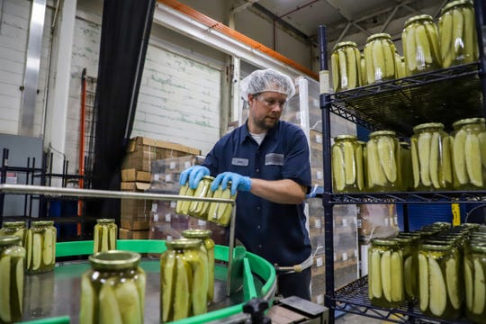 Sam Nason, 38, of Oak Park is the director of production at McClure's Pickles plant in Detroit and grabs the finished jars of pickles at the end of the production line on Wednesday, Nov. 13, 2019.