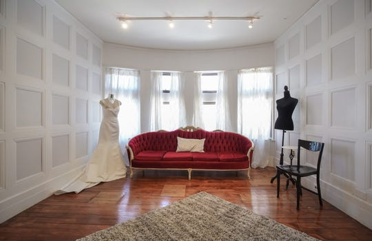 Another bedroom is set up for a bride to debut her dress. To get to these original wood floors, the owner had to pull up one layer of carpet, then a second layer of carpet, then the  vinyl floor underneath.