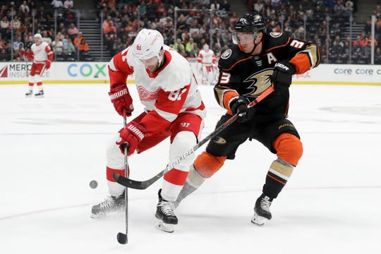 Anaheim Ducks right wing Jakob Silfverberg knocks the puck away from Detroit Red Wings center Frans Nielsen during the first period in Anaheim, Calif., Tuesday, Nov. 12, 2019.