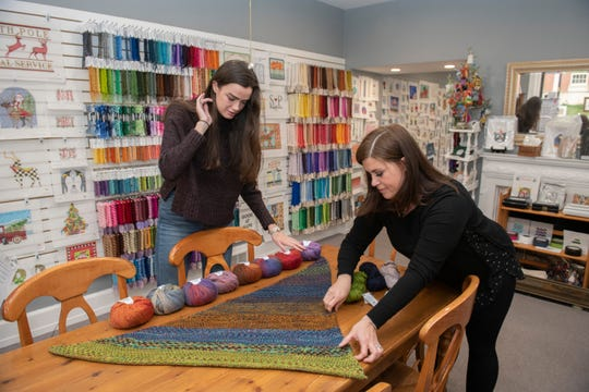 E-commerce and social media intern Kaley MacLeod (left) and yarn manager Elizabeth Wakefield arrange a display of yarn and a hand-knitted shawl called 'Nightshift,' designed by Andrea Mowry (not pictured) and knitted by Wakefield inside The Wool and The Floss knitting shop.