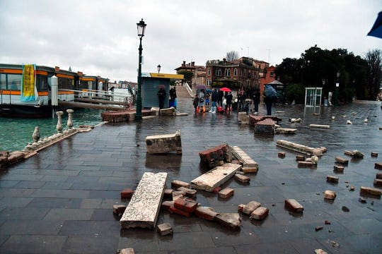 Parts of a dock lie damaged, in Venice, Italy, Wednesday, Nov. 13, 2019. The mayor of Venice is blaming climate change for flooding in the historic canal city that has reached the second-highest levels ever recorded, as another exceptional water level was recorded Wednesday.