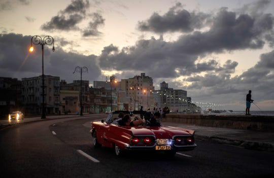 In this Nov. 10, 2019 photo, tourists take a joy ride along the malecon sea wall in Havana, Cuba. The city of Havana will celebrate its 500th anniversary on Nov. 16.