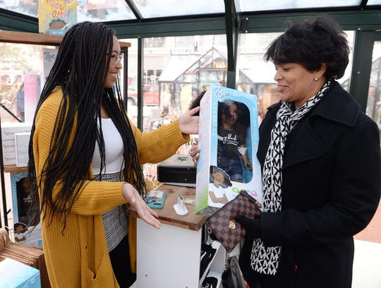 Tamiko Christian, right, of West Bloomfield,  purchases a Zoe doll for her granddaughter Wednesday from Yelitsa Jean-Charles, left, founder and CEO of Healthy Roots at the Downtown Detroit Markets.