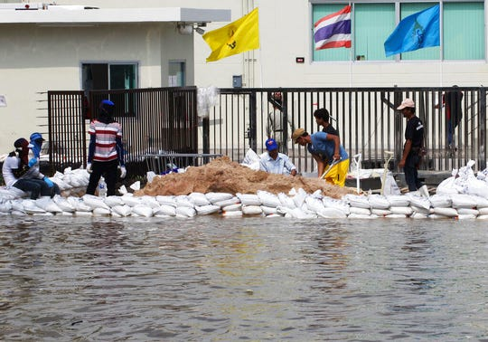 In this Oct. 9, 2013, file photo, workers build a water barrier with sandbags as floodwater threaten their factory at Amata Nakorn industrial estate in Chonburi province, eastern Thailand.