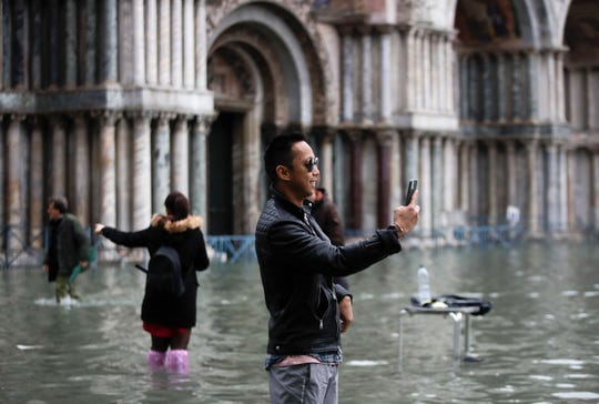 Tourists take pictures in a flooded St. Mark's Square, in Venice, Wednesday, Nov. 13, 2019.