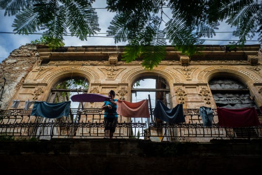 In this Nov. 10, 2019 photo, a woman pulls towels off the line after they dried on the balcony of an old home, missing part of its roof, in Havana, Cuba.