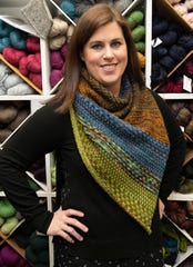 Yarn manager Elizabeth Wakefield wears a hand-knitted shawl called 'Nightshift,' designed by Andrea Mowry and knitted by Wakefield inside The Wool and The Floss knitting shop in Grosse Pointe.