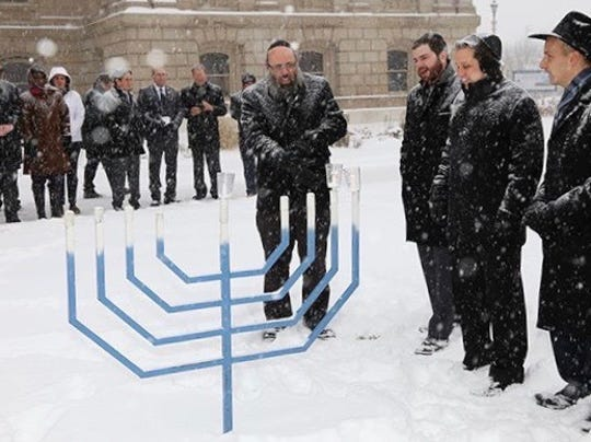 State lawmakers and others gather around menorah outside the Michigan Capitol during a past holiday season.